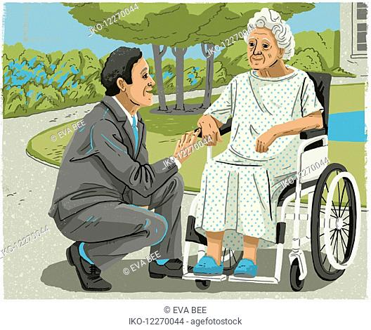 Man in suit talking to elderly woman in wheelchair