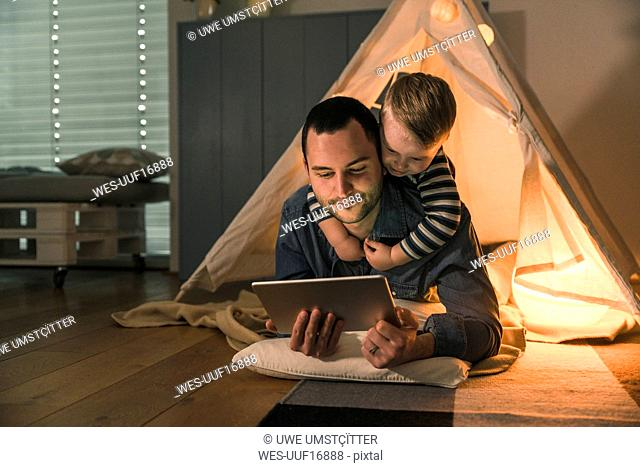 Father and son sharing a tablet at an illuminated tent at home