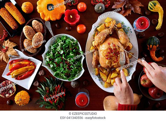 Thanksgiving traditional food on the table decorated with gourds, berries, chestnuts, leaves and candles. Flat lay, overhead shot