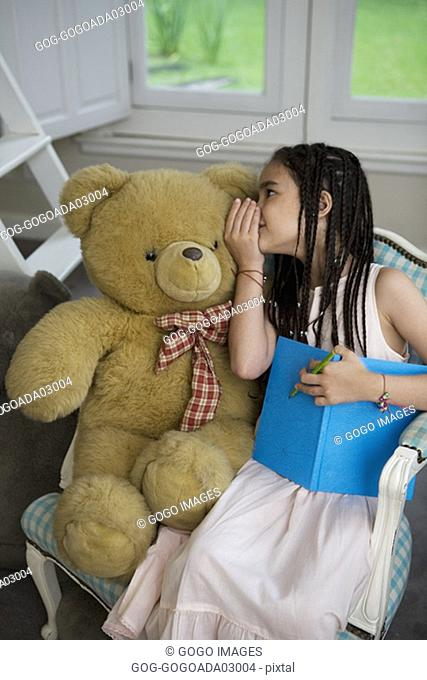 Young girl whispering to stuffed bear