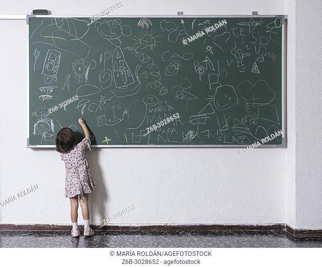 little girl drawing on a big chalkboard