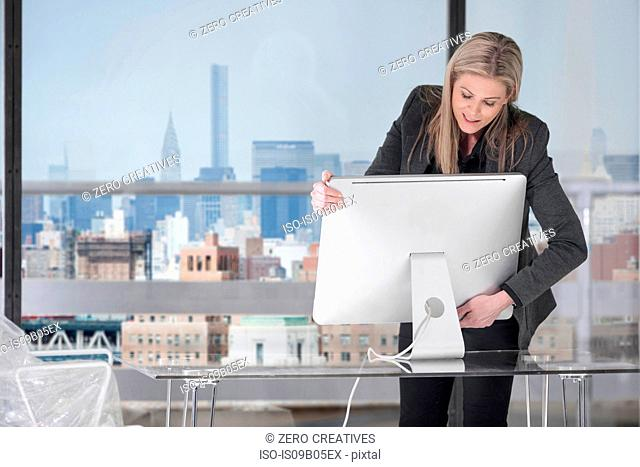 Businesswoman setting up computer in office