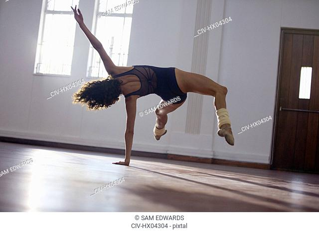 Graceful, strong young female dancer practicing in dance studio