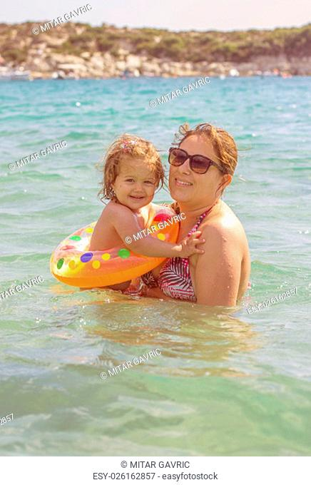 Happy Young Mother and her little girl have fun in the beautiful turquese sea on summer day. Travel Vacation lifestyle