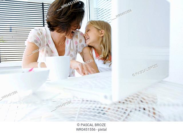 Close-up of a mid adult woman with her daughter smiling