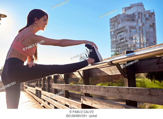 Woman stretching in city park, Barcelona, Catalonia, Spain