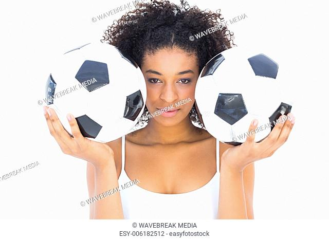 Pretty girl holding footballs and looking at camera