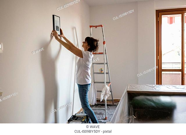 Senior woman putting picture frame on house interior white wall