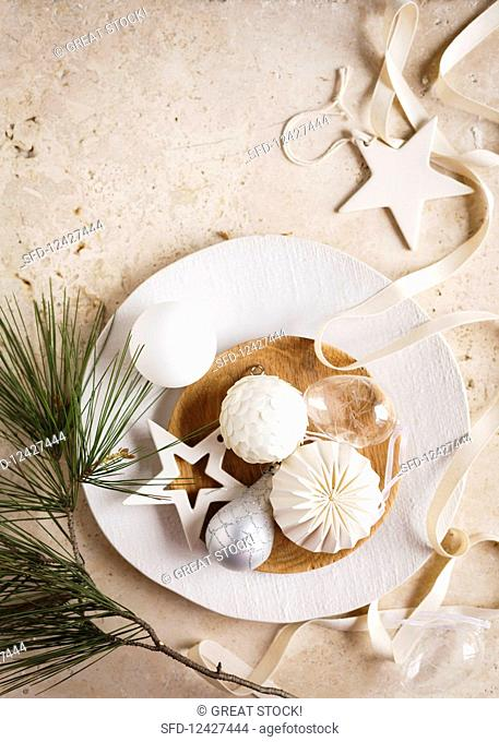 Christmas decorations on a white plate with a wooden bowl