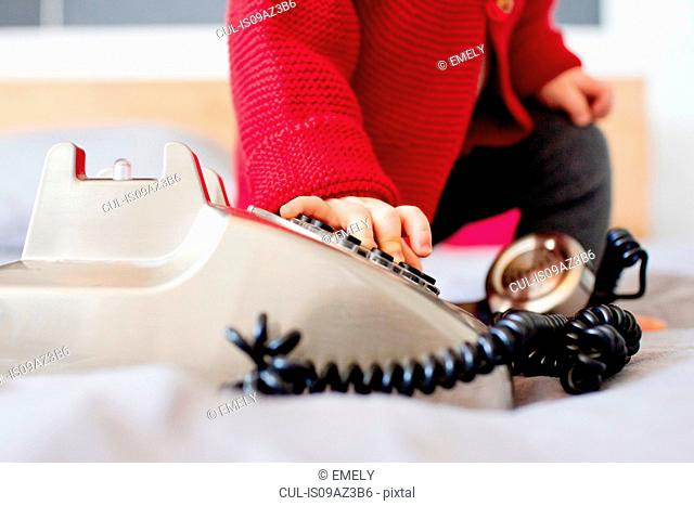 Cropped shot of baby girl dialling landline telephone