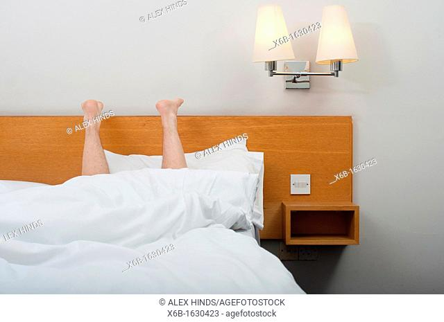 Legs pointing up from under bed covers