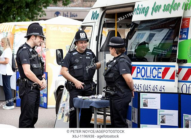 policemen and women by police rural communities mobile office van in town high street