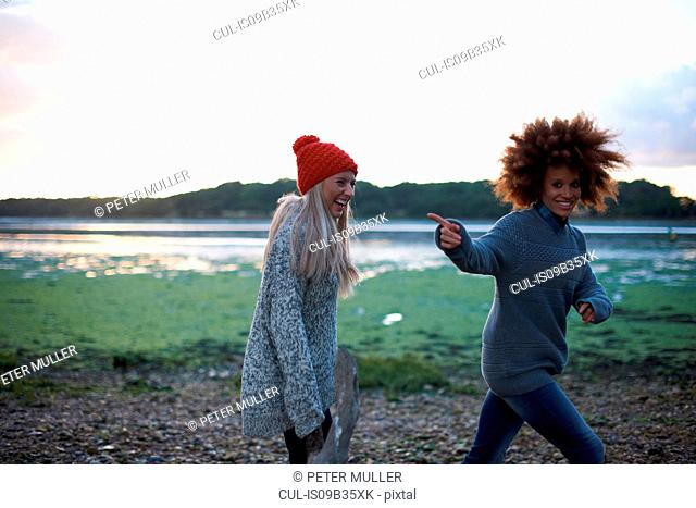 Two young women laughing by sea at sunset