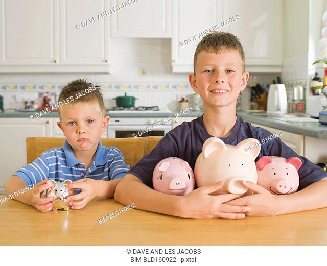 Competing Caucasian brothers with piggy banks on kitchen table