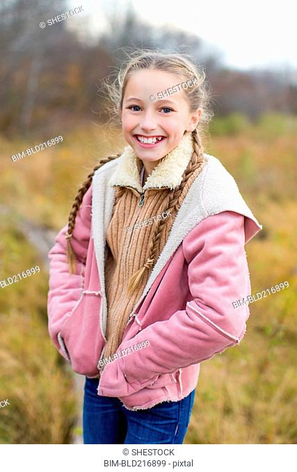 Smiling girl standing with hands in pockets in field