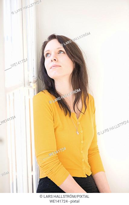 Woman sitting by window, looking up. Lifestyle image showing a confident woman thinking. Concept of contemplation