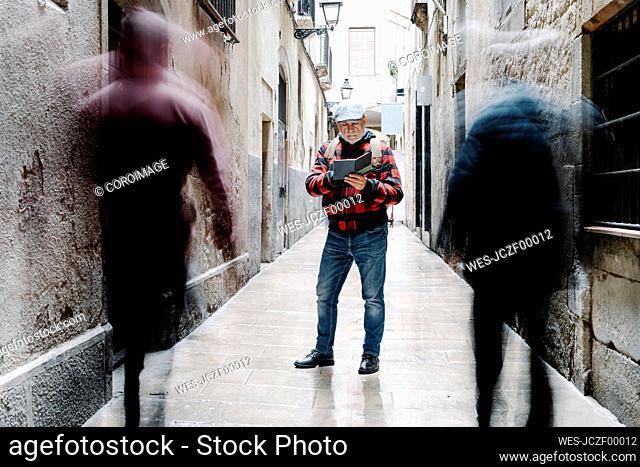Senior man using guidebook in the city, Barcelona, Spain