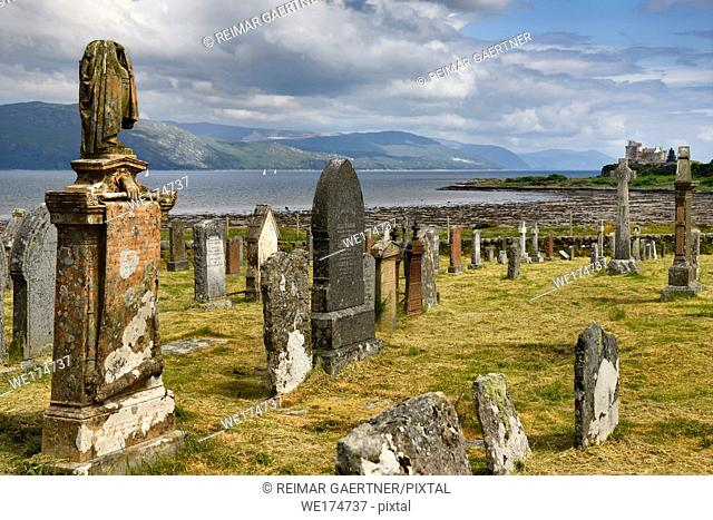Ancient tombstones at Kilpatrick Cemetery next to Duart Castle on Isle of Mull with sailboats on Sound of Mull at Loch Linnhe Scotland UK