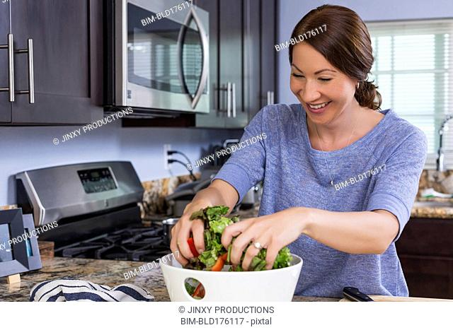 Mixed race woman tossing salad in kitchen