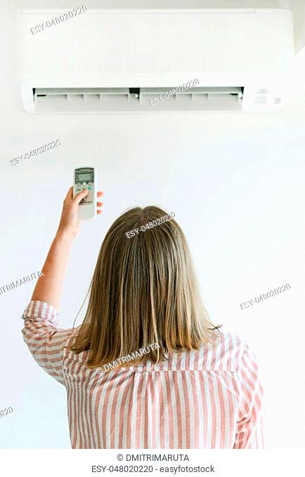 Woman holding remote control aimed at the air conditioner