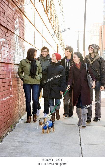 Group of friends walking on urban sidewalk