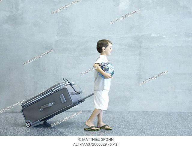 Boy with suitcase and globe