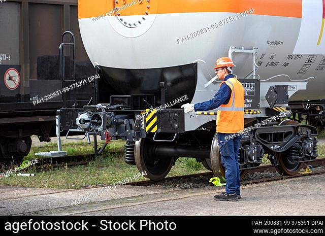 31 August 2020, North Rhine-Westphalia, Minden: DB shunting attendant Tjaard Wehrend, stands next to a new digital automatic coupling (DAK) for freight trains...