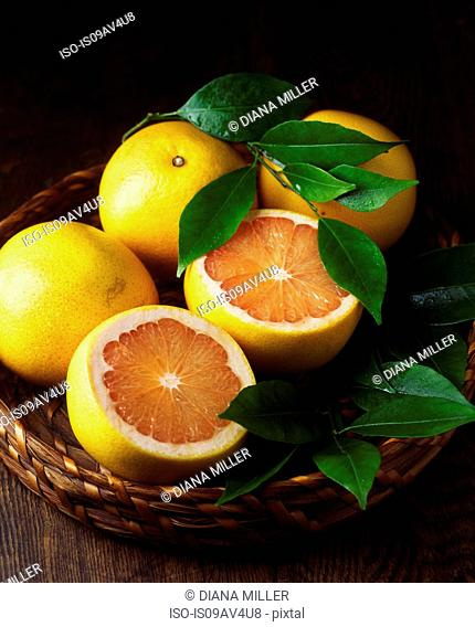 Whole and sliced grapefruit and leaves in wicker basket