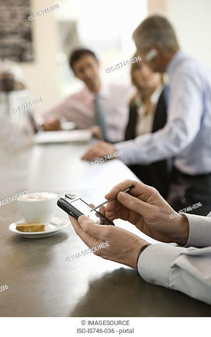 Man using handheld computer at bar counter