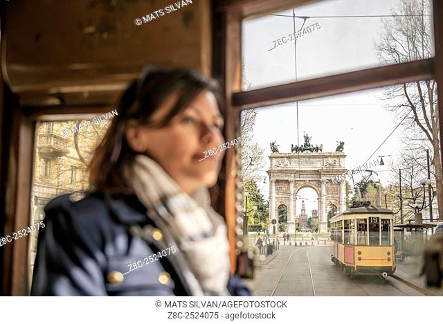 Woman travel in a tram and in background Arco della pace and castle Sforza in Milan, Italy