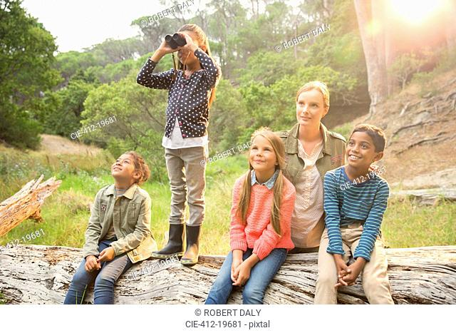 Students and teacher using binoculars in forest