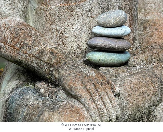 A stack of stones resting in the hands of Buddha in a garden in County Westmeath, Ireland