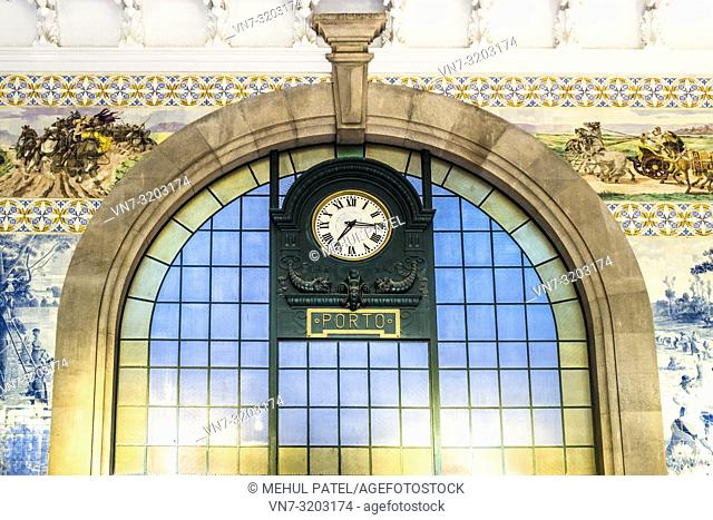 Colourful wall tiles and main clock Inside São Bento train station (Estação São Bento) - Porto, Portugal