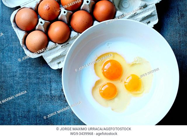 Uncooked eggs in bowl and egg box