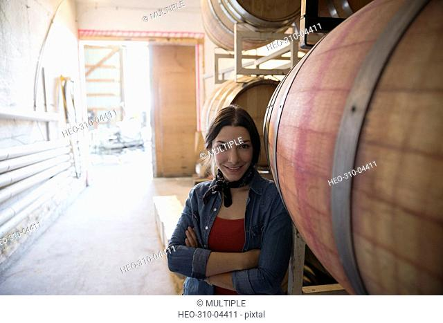 Portrait confident female vintner in winery barrel room
