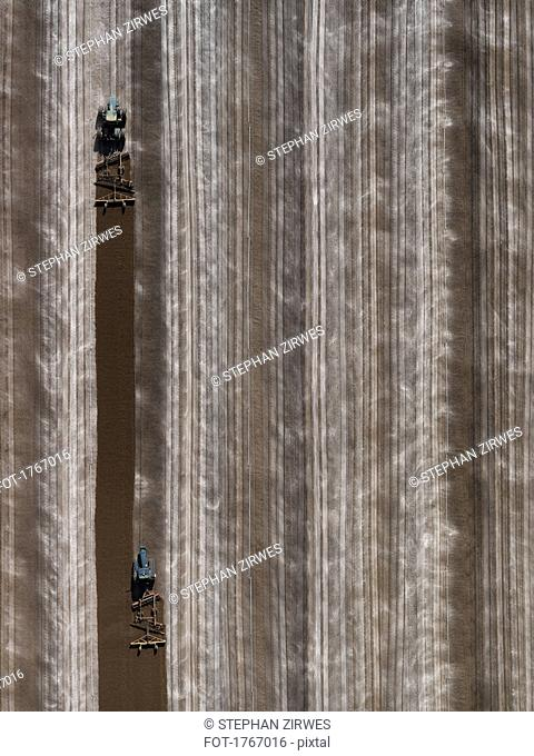 Aerial view agricultural tractors plowing field, Bakersfield, California, USA