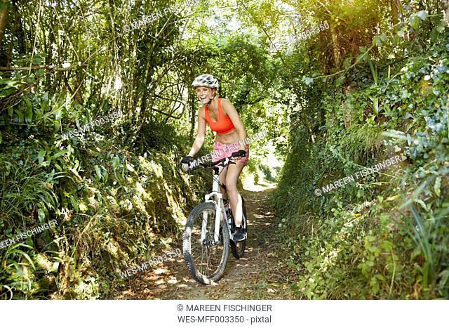 Young woman riding mountainbike on a trail