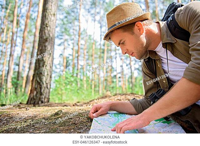 Cheerful male tourist is looking at map with concentration. He is sitting in the nature