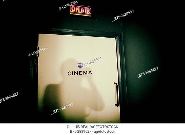 'Cinema' sign on door, with light reflection. London, England