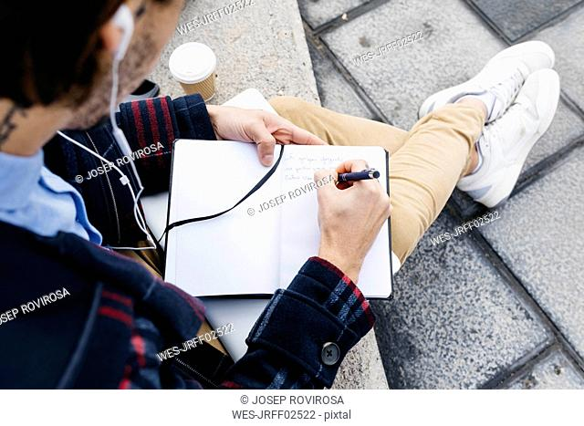 Man sitting outside taking notes