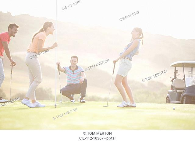 Friends laughing near hole on golf course