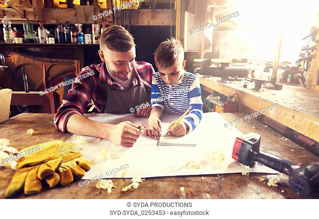 happy father and son with blueprint at workshop