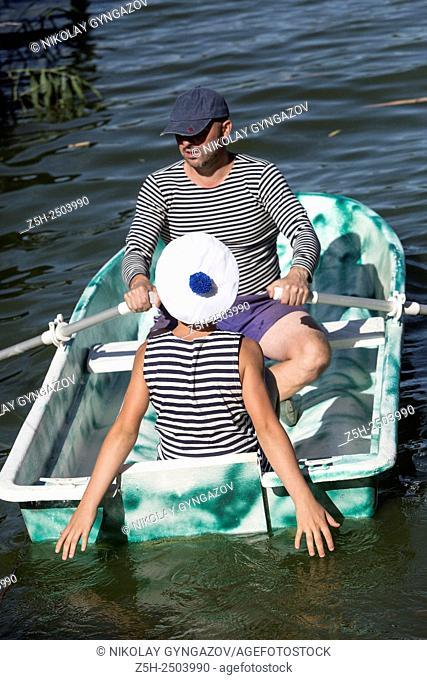 Russian Federation. Belgorod region. A man with a boy in a striped vest on boat trips