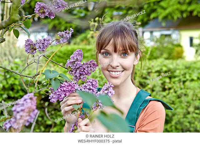 Germany, Cologne, Portrait of young woman holding lilac flowers, smiling