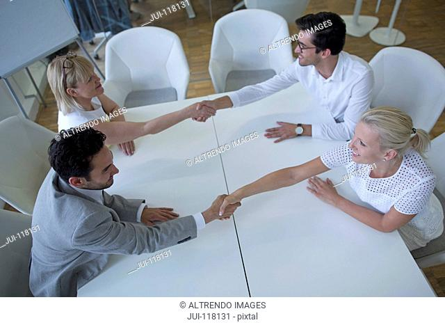 Overhead View Of Businesspeople Shaking Hands In Meeting