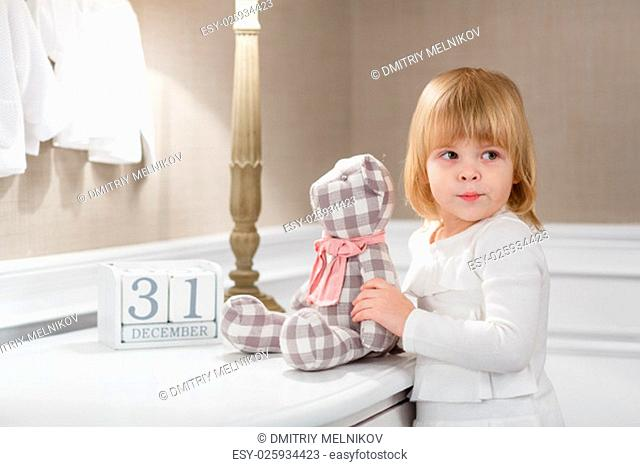 Happy sweet little girl with date 31 december stands in the room . Eve of New Year