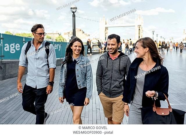 UK, London, happy friends walking near  Tower Bridge