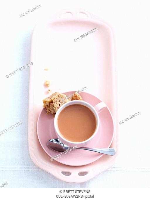 Overhead view of teacup and saucer on high tea dish with eaten sandwich