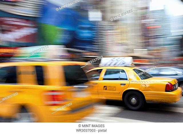 Yellow cabs driving on street near Times Square in Manhattan, New York, USA, motion blur