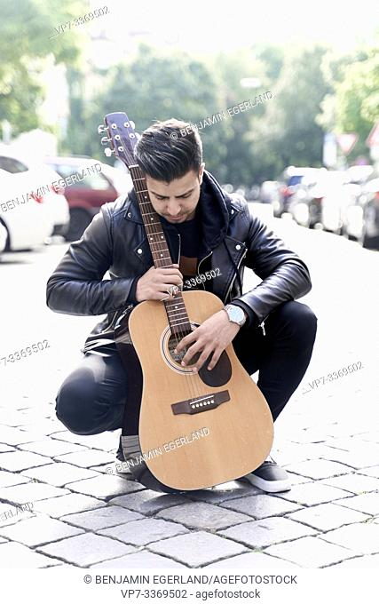 Afghan man with acoustic guitar in hands at street in city Munich, Germany